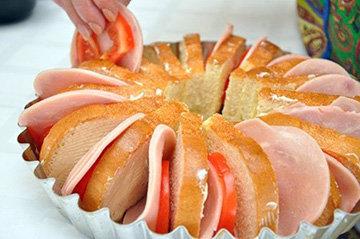 Положить кусочек помидора, ломтик сыра и ветчины между ломтиками хлеба
