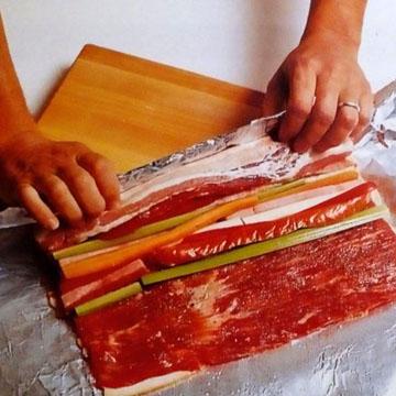 При помощи фольги мясо с начинкой свернуть в рулет
