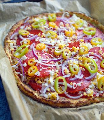 Пиццу вынуть - смазать томатным соусом и положить начинку.