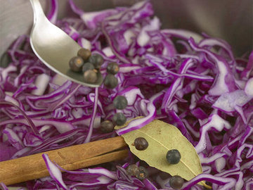 Добавить красную капусту, лавровый лист, ягоды можжевельника и палочку корицы
